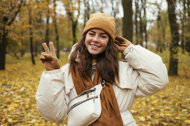 Happy young woman peace gesturing in autumn park