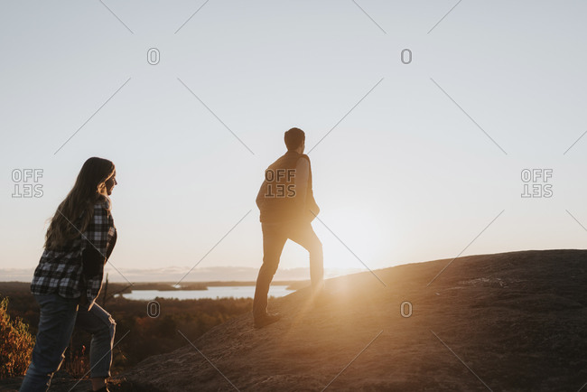 Young couple walking up hill against setting sun