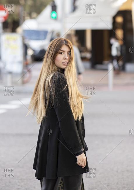 Woman wearing jacket standing on street in city