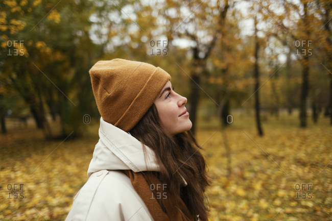 Smiling young woman day dreaming in autumn park