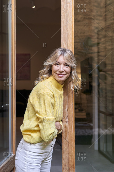 Smiling mature woman leaning on doorway at home