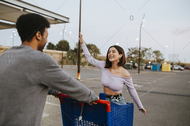 Carefree woman sitting in shopping cart by man