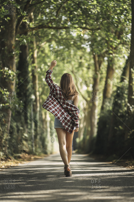 Playful woman with hand raised walking on road