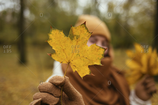 Young woman showing autumn leaf in public park
