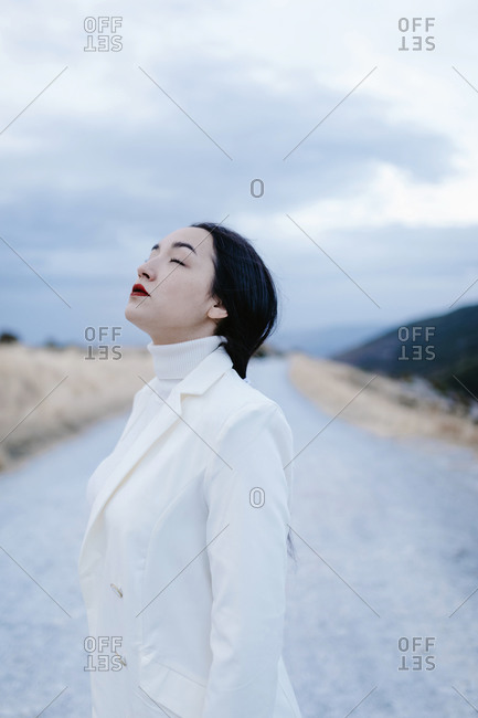 Young woman with eyes closed standing on road