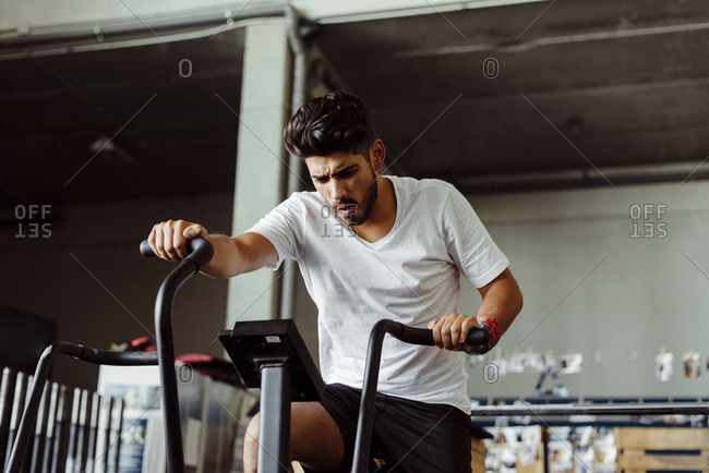 Young sportsman exercising on air bike at gym