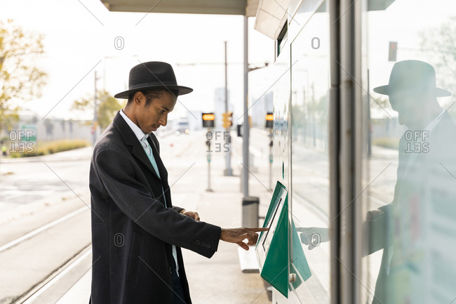 Young man using ticket machine at tram stop