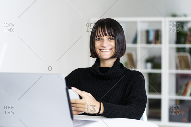 Happy young woman with laptop in study room