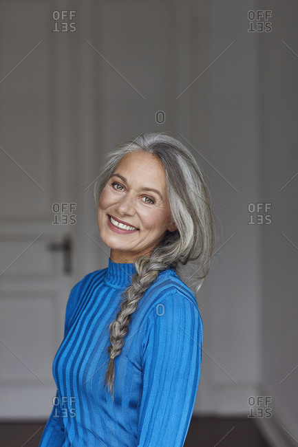 Smiling mature woman with gray hair at home