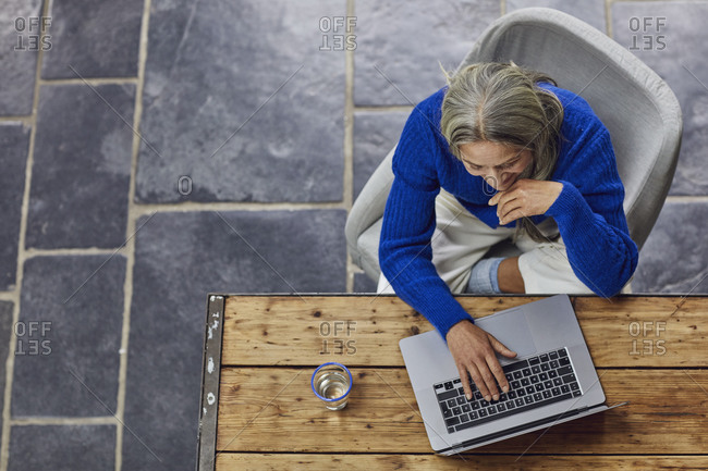 Mature woman using laptop at table in home