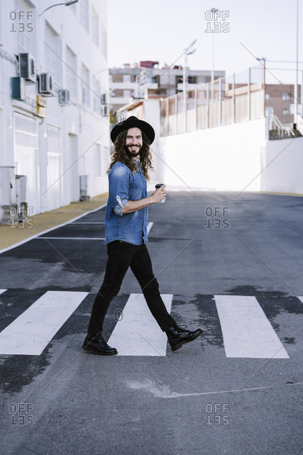 Happy young man walking on street in city