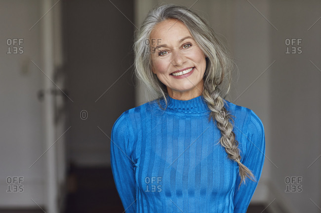 Happy mature woman with gray hair at home