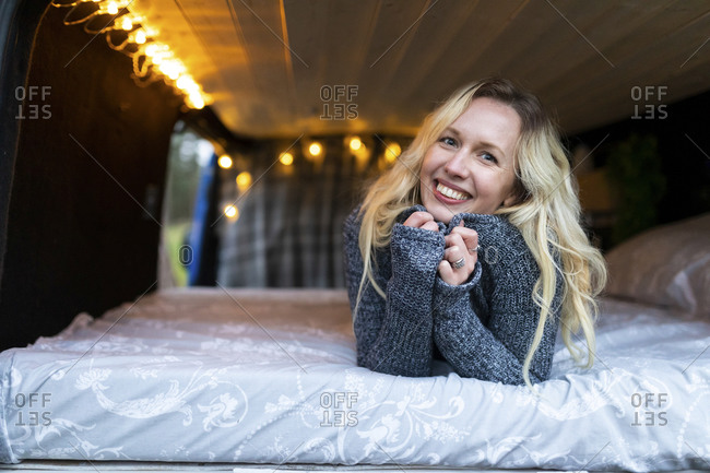 Smiling woman lying on bed in camper van