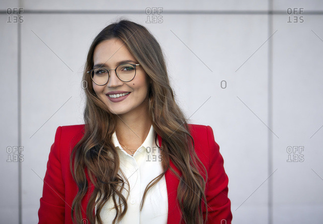 Smiling businesswoman wearing eyeglasses smiling while standing against wall