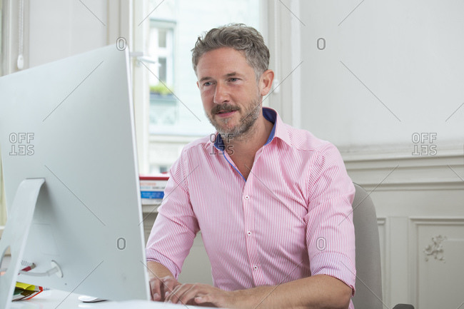 Elegant businessman concentrating while working on computer at office