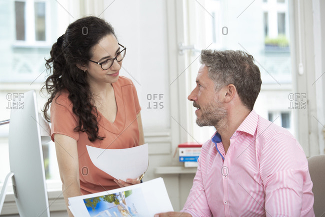 Smiling female professional discussing with male colleague in office
