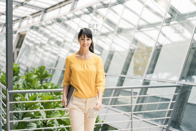 Confident female entrepreneur walking with laptop in office corridor