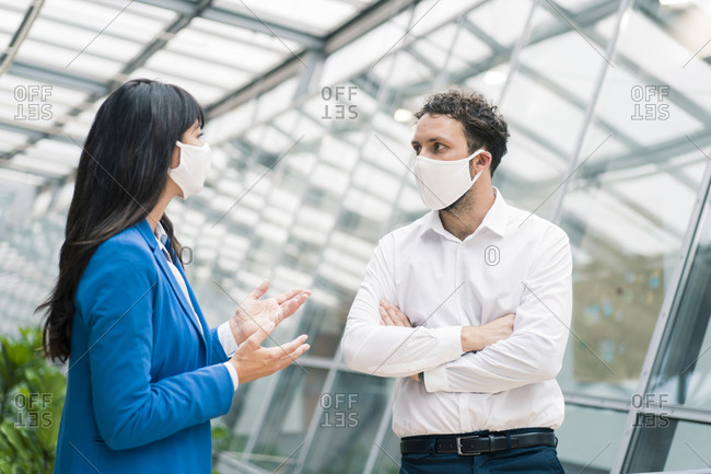 Male and female professionals discussing in meeting during COVID-19
