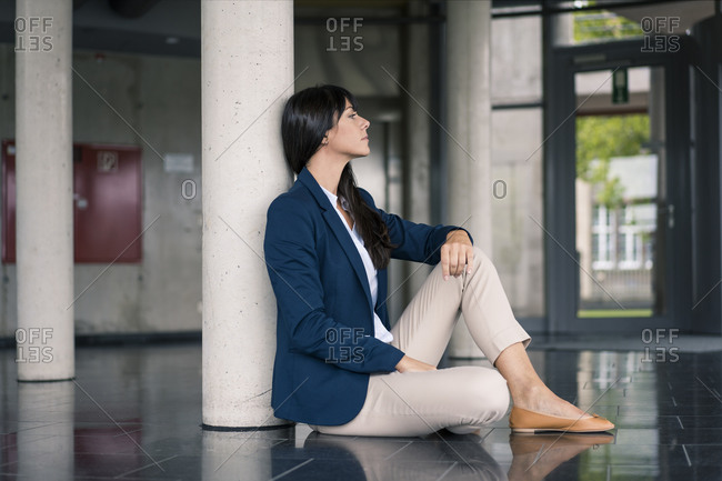 Businesswoman contemplating while sitting by column in office lobby