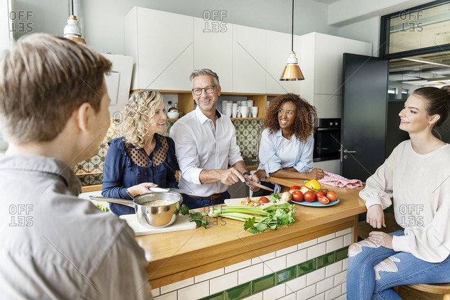 Smiling business colleagues talking while cooking in office kitchen