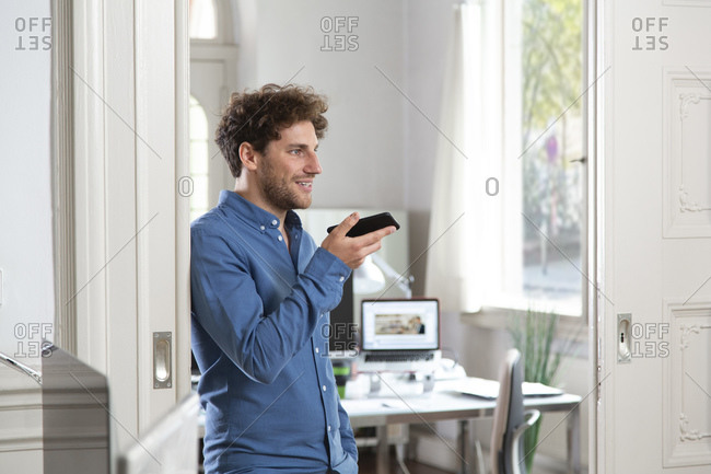 Male professional sending voicemail through mobile phone at office