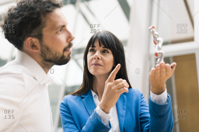 Businessman analyzing model standing by female colleague in office