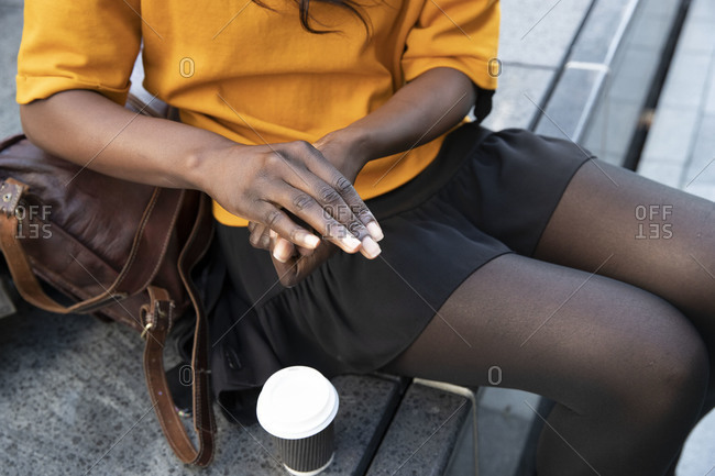 Female professional sitting with hands clasped and disposable cup