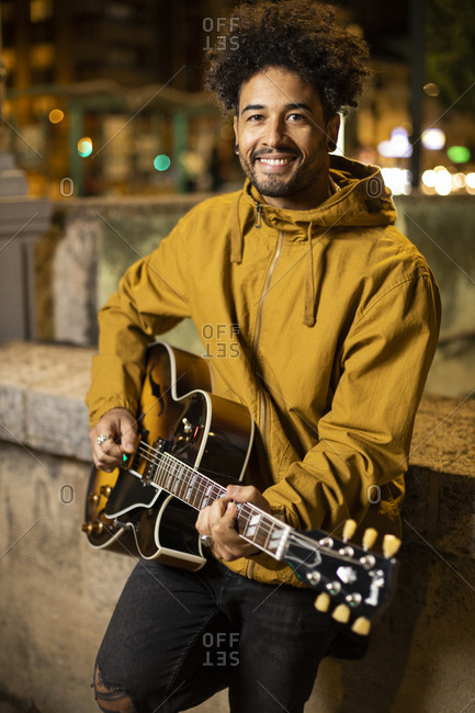 Guitarist smiling while playing guitar leaning on retaining wall