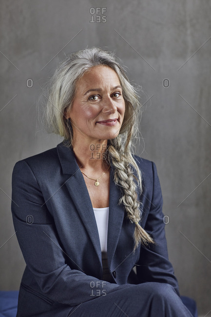 Smiling female professional in business casual against gray wall