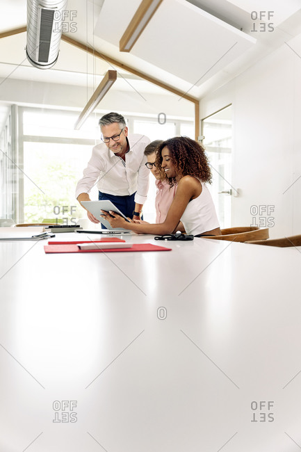 Business colleagues using digital tablet in meeting at boardroom