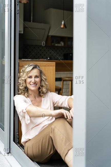 Happy female entrepreneur sitting at doorway of office cafeteria