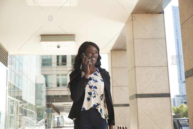 Businesswoman talking on mobile phone while standing at corridor