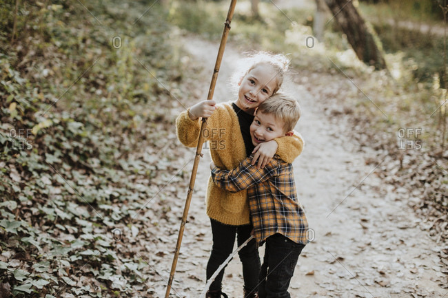 Sister holding stick while embracing brother standing in forest