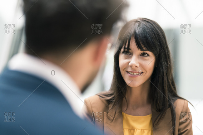 Smiling female entrepreneur looking at male colleague in office