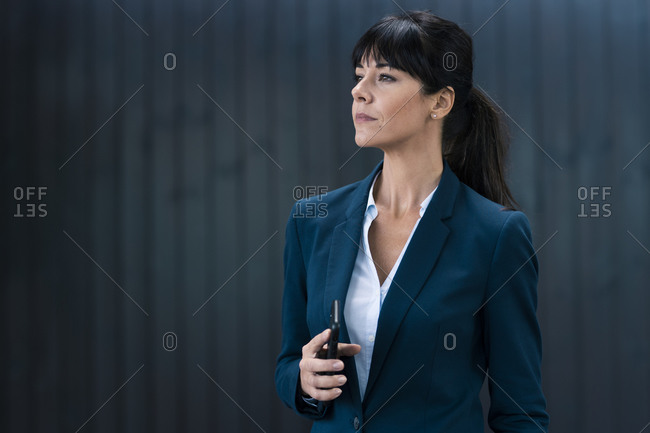 Female professional with mobile phone looking away against wall