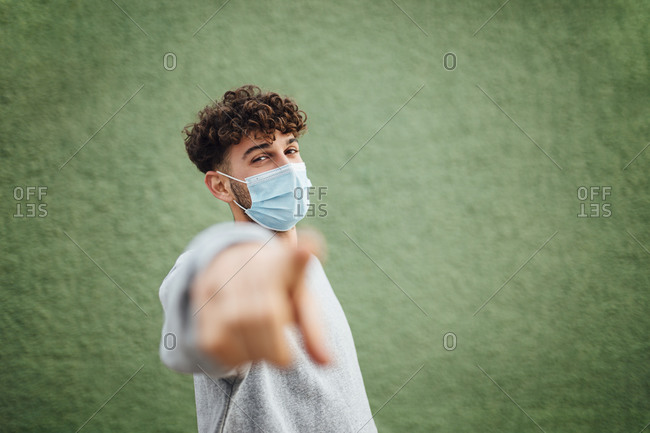 Man pointing while standing by green background during pandemic