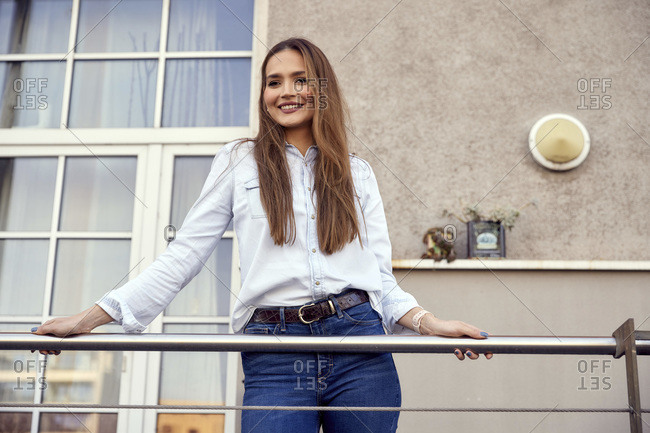 Business woman wearing casual smiling while standing in balcony