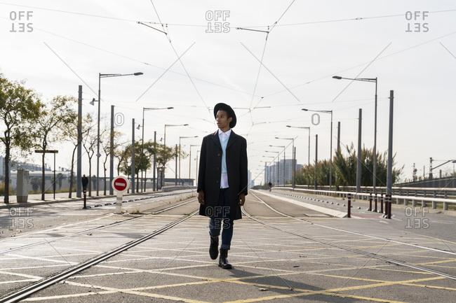 Fashionable young man walking between railroad track on street