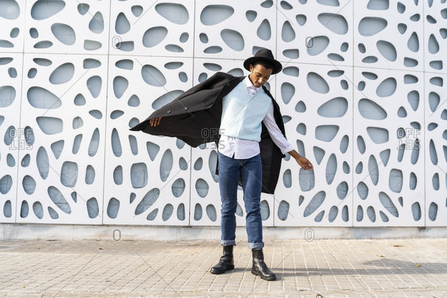 Young man with arms outstretched standing against pattern wall