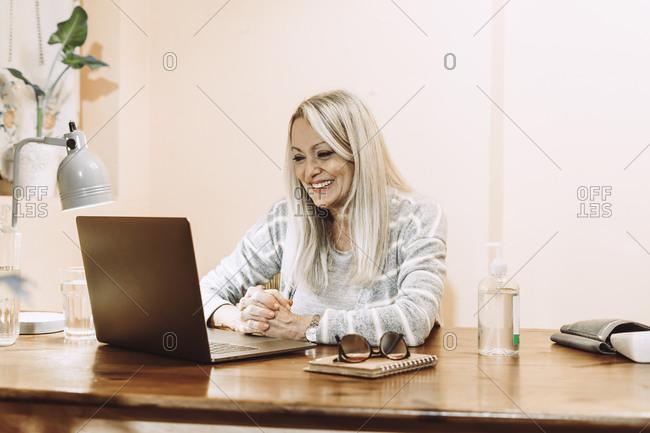 Happy senior taking online consultation through laptop at home