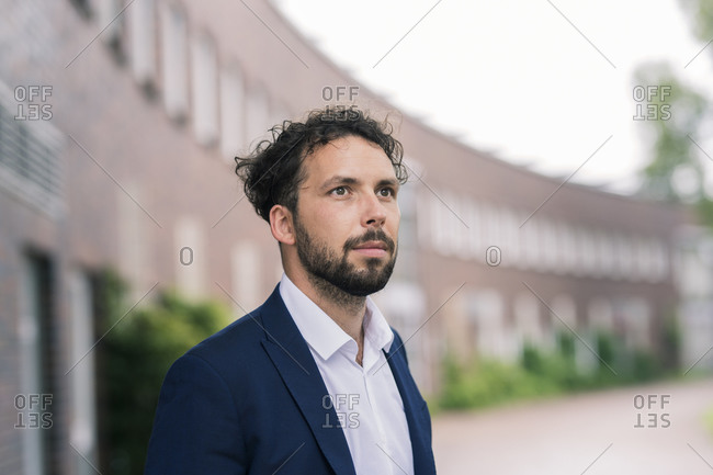 Male professional looking away outside building in office park