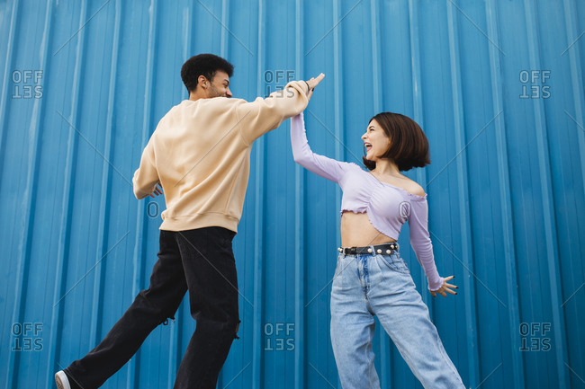 Happy couple giving high-five while standing against blue wall
