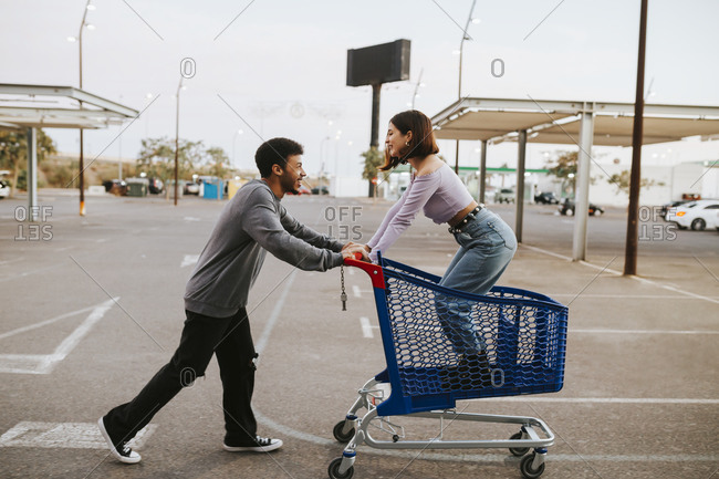 Boyfriend pushing girlfriend standing in shopping cart on road
