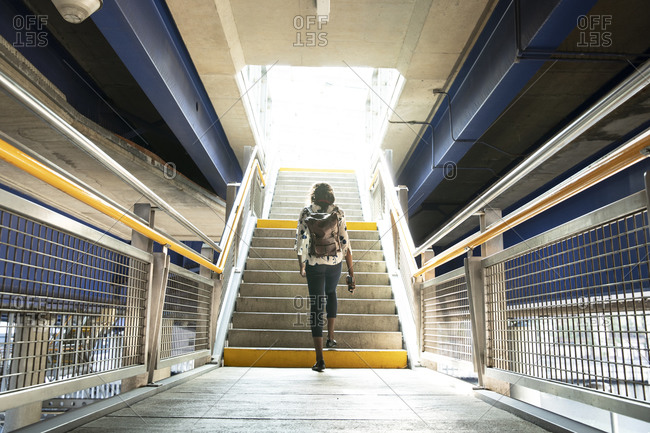 Businesswoman with backpack walking on steps in subway station