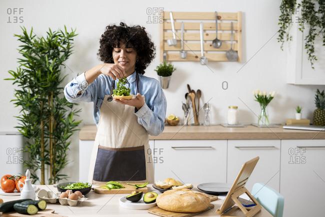 Portrait of young woman preparing vegan sandwiches in kitchen