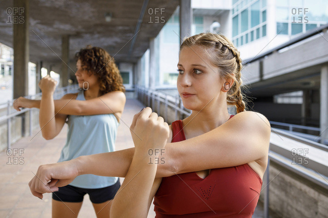 Sportswomen doing warm up exercise while stretching on bridge
