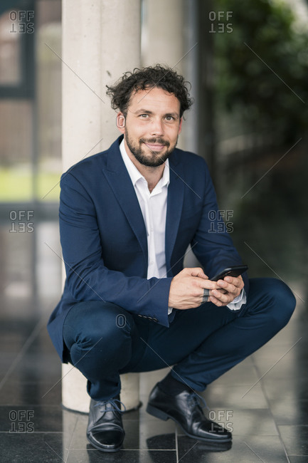 Male entrepreneur crouching with mobile phone at office lobby