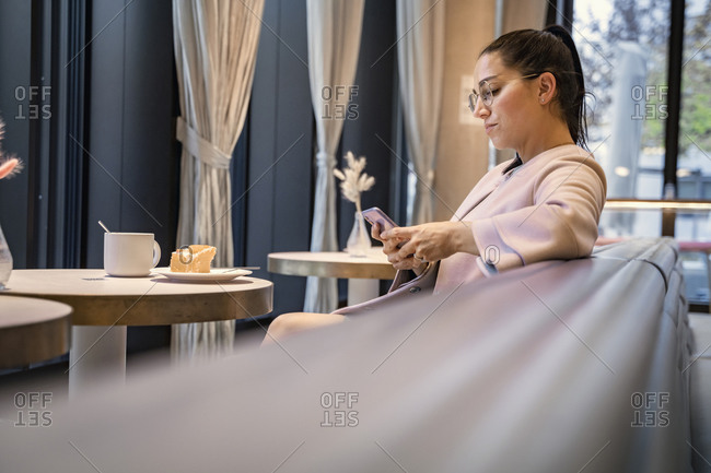 Businesswoman using mobile phone while sitting at modern cafe