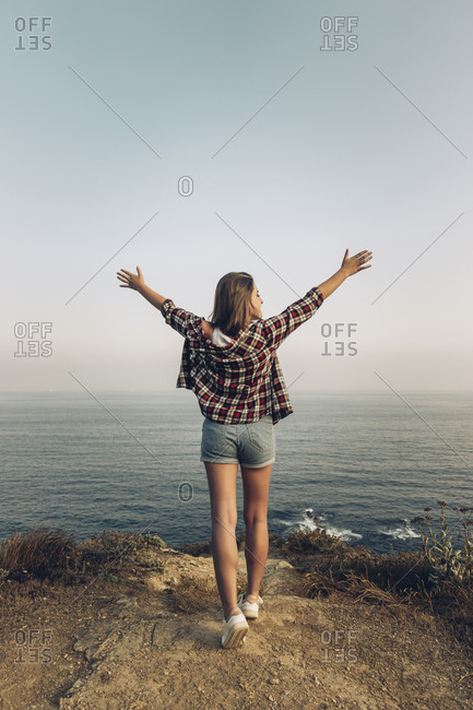 Young woman with arms outstretched standing against clear sky