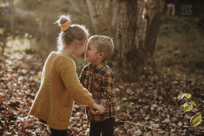 Sibling rubbing noses while holding hands standing at forest